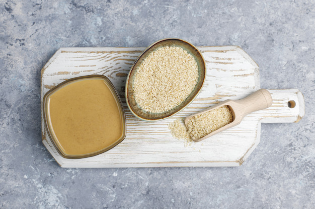 Bowl of tahini with sesame seeds on concrete background