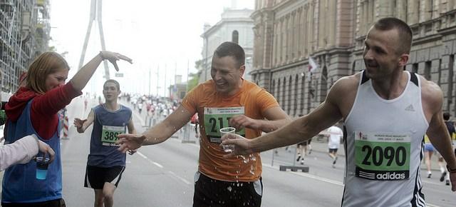 Runners grabbing water during a marathon