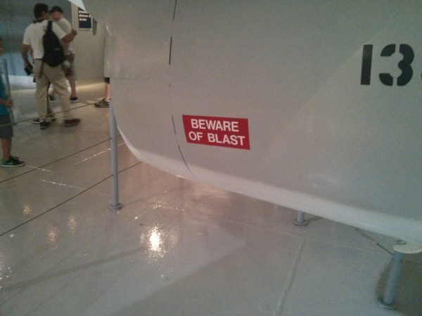 Warning sign near the rear of a Navy jet.