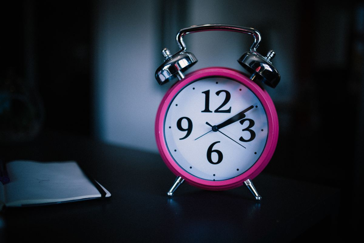 A small pink analog alarm clock