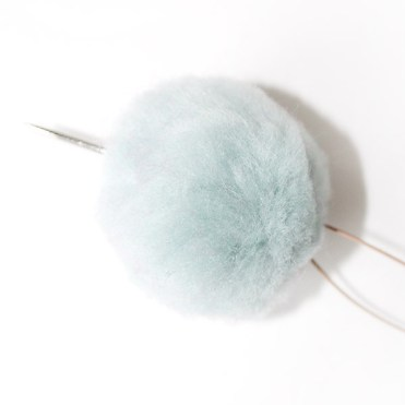 Thread the needle with leather cord and run it through the pom.