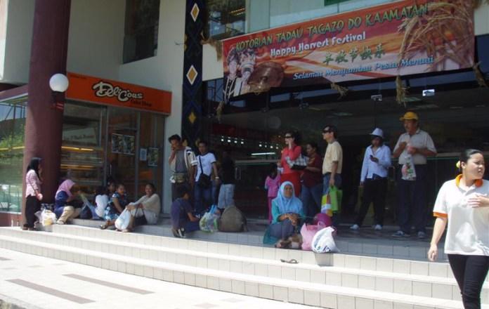 Znavení nakupující před jedním z četných obchodních center čekají na autobus
