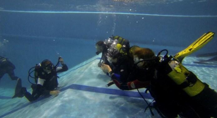 Lubor Hubáček pantomimicky pod vodou vysvětluje, jak se nafukuje a vyfukuje žaket.