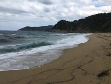 Pláž a rozbouřené moře.