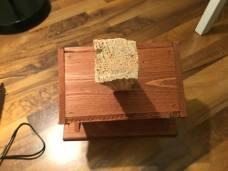 Dřevo s lepidlem umístěte doprostřed dna budky