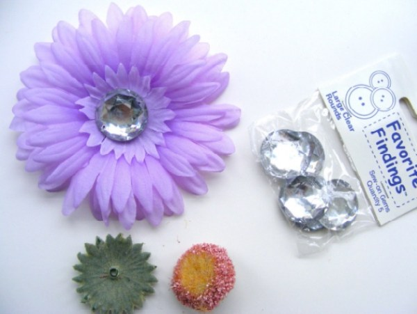 Artificial daisy with a package of crystal buttons.