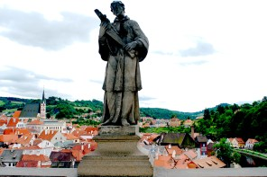 Statue on bridge over red roofs