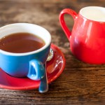blue tea cup with red saucer and red milk jug