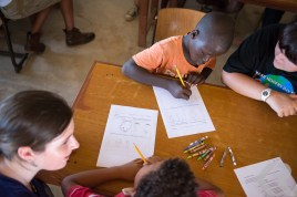 American students help orphans in Ghana write letters.