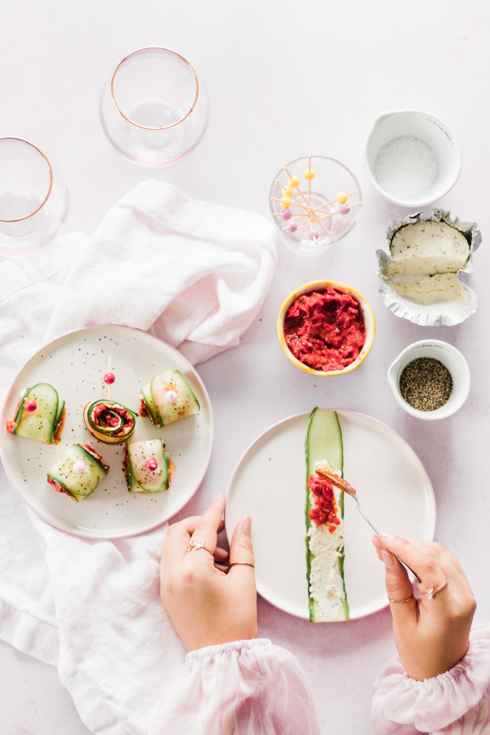 Holiday Appetizer: Cucumber Rolls — Making the holidays a breeze with these simplecanapésfilled with Boursincheese, piquillo pepper bruschetta, and a little salt and pepper! #appetizer #christmasrecipes #appetizerseasy #vegetarianrecipes #dinnerpartyrecipes