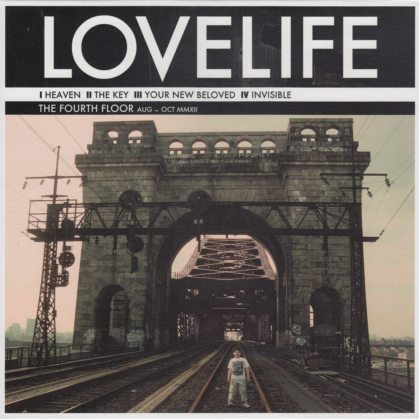 "The cover image of the band Lovelife's single ""Your New Beloved."" Across the top is a black banner reading ""Lovelife"" in bold white lettering. Beneath the band name, it reads the song titles on the single: ""1. Heaven 2. The Key 3. Your New Beloved 4. Invisible."" Beneath the song titles it reads ""The Fourth Floor Aug ~ Oct MMXII"". Below all the text is an image of a tall stone arch leading to a bridge. The bridge is lined with railroad tracks. At its center stands a chubby boy."