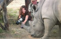 African wildlife and travel presenter with rhino in Zimbabwe