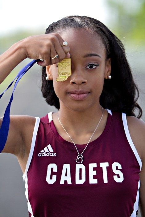 Young track and field runner with medal