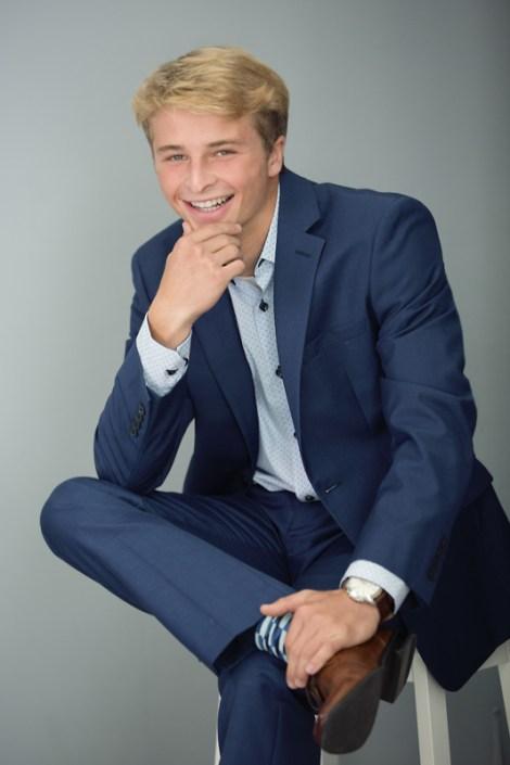 Portrait of a high school senior boy smiling in a blue suit