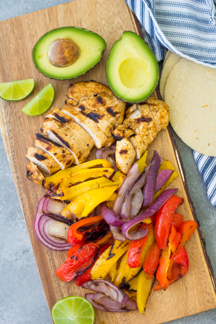 Grilled chicken, peppers and onions, and avocado on a wood board.