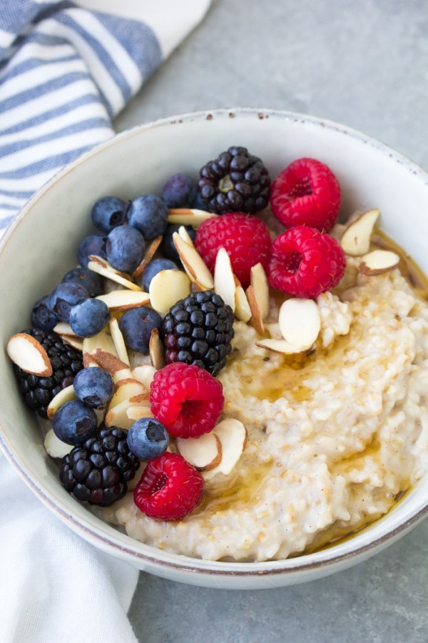 Creamy steel cut oatmeal with berries, almonds and maple syrup. How to cook steel cut oats for meal prep breakfasts.