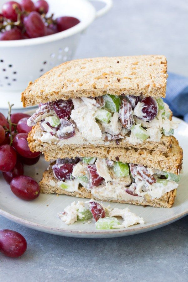 Chicken salad recipe with grapes and pecans stacked on plate