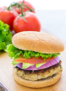 Homemade turkey burger with lettuce, tomato, avocado and red onion.