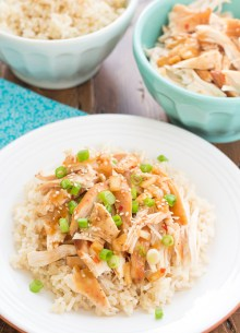 Crockpot honey sesame chicken served with brown rice and green onions.