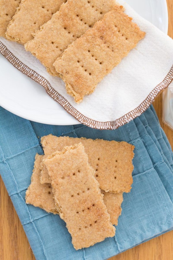 Homemade graham crackers on a blue napkin and on a plate.