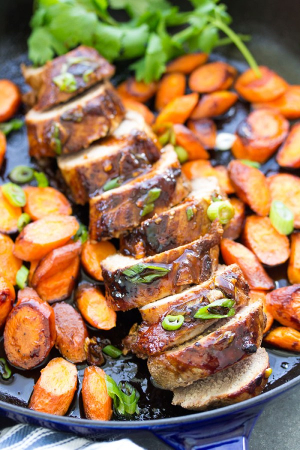 Roasted pork tenderloin recipe with honey hoisin marinade, in a skillet with carrots on the side.