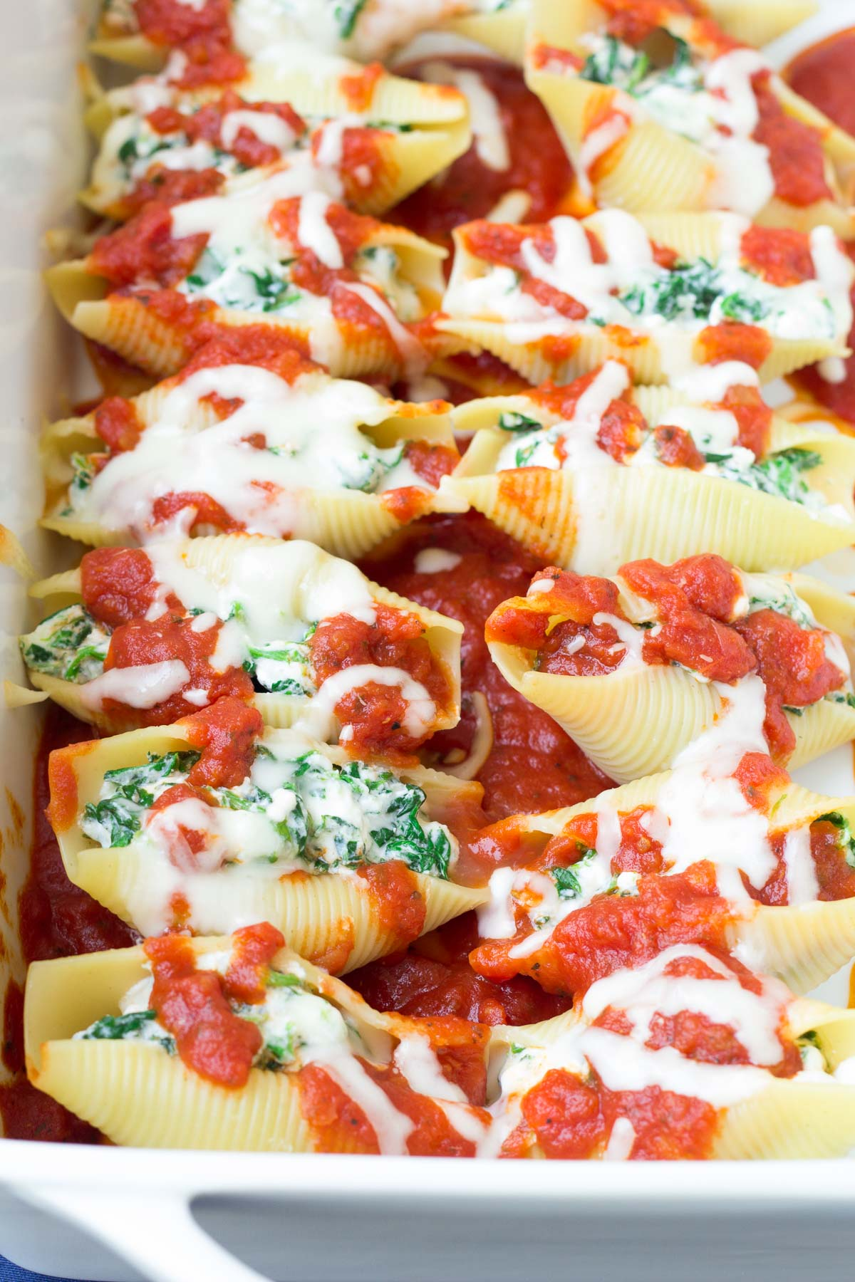 stuffed shells in a dish with cheese and marinara sauce