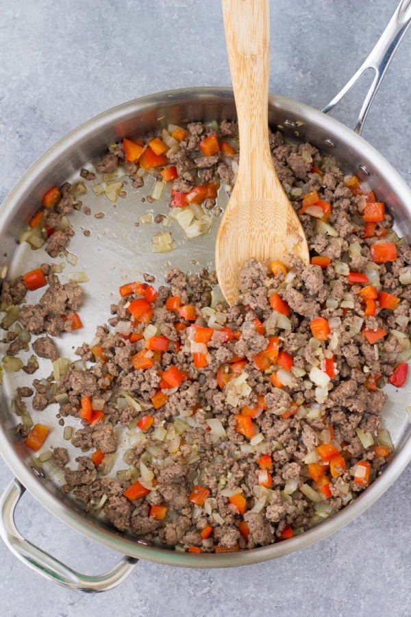 Cooking onion, bell pepper and ground beef in a skillet.