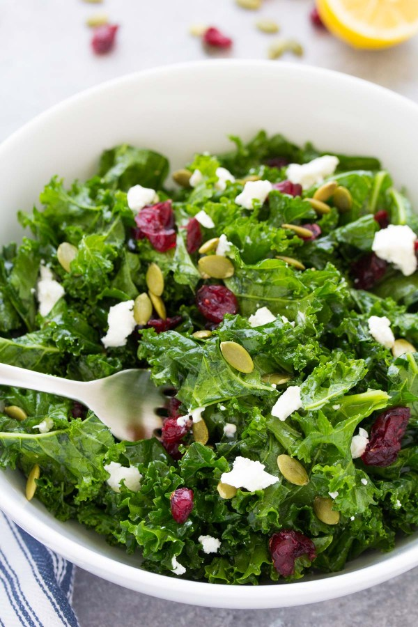Massaged kale salad with cranberries, pepitas and goat cheese in a bowl with a fork.