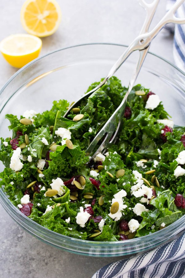 Massaged kale salad in a serving bowl with salad tongs.