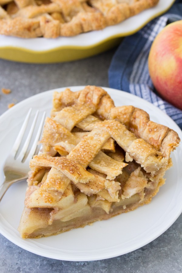 Slice of homemade apple pie from scratch with a lattice pie crust.