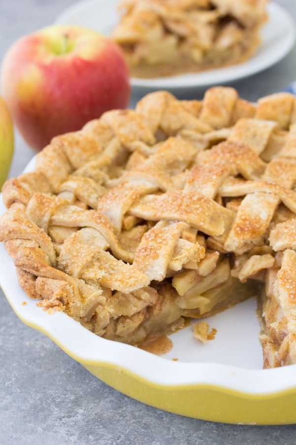 Side view of an apple pie with a slice cut out. You can see the juicy apple pie filling and the lattice top pie crust.