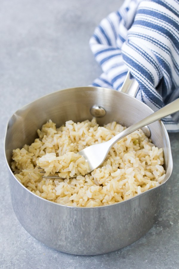 How to cook brown rice on the stove. Fluffy brown rice in a pot with a fork.