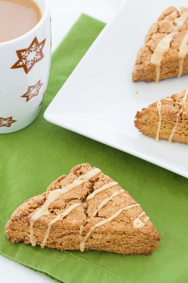 Gingerbread scone on a green napkin, next to a cup of coffee.