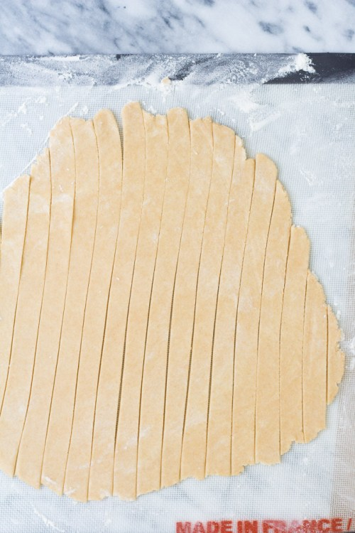 Rolled out dough round cut into strips for a lattice pie crust.