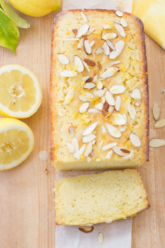 overhead view of pound cake on cutting board sliced with sliced lemon on side