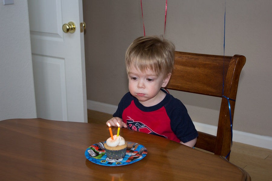 2 year old boy eating cupcake at birthday