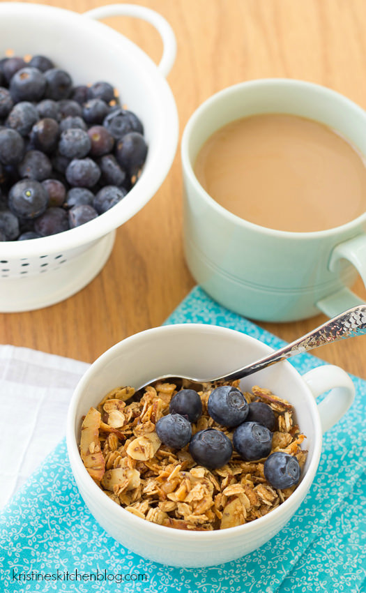 close up of honey almond flax granola in small white bowl with blueberries