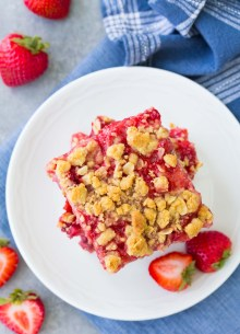 Overhead view of strawberry oatmeal bars stacked on a small white plate.