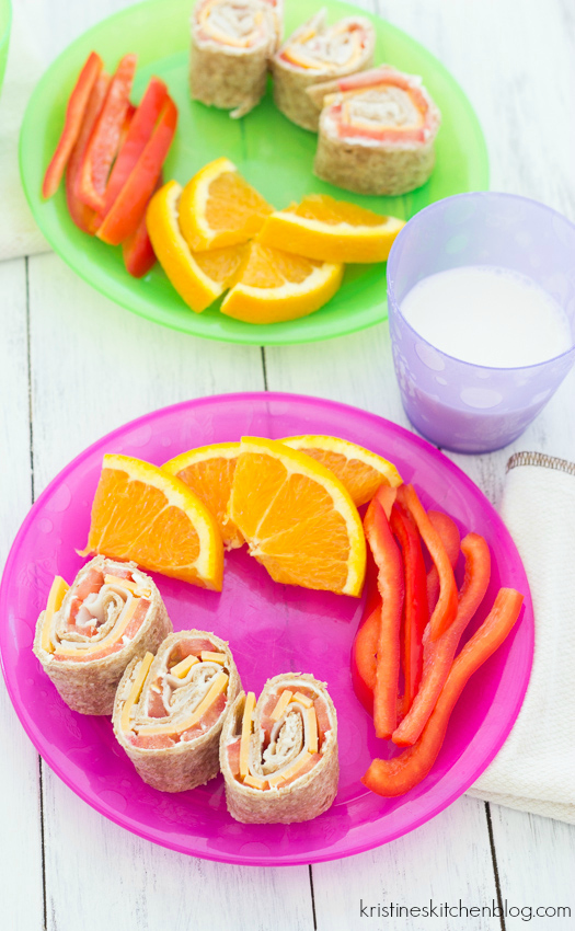 pinwheels on a plate with orange slices and red bell pepper
