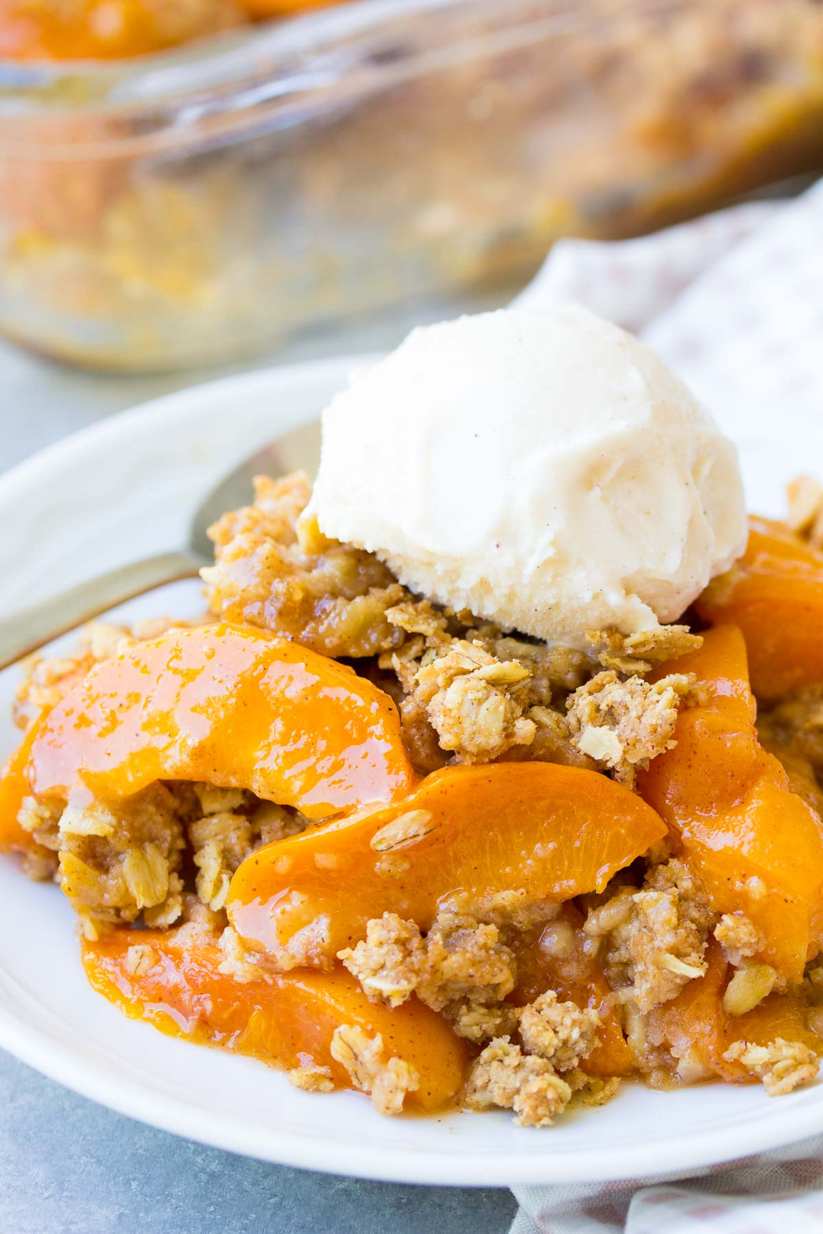 Close up of fresh apricot crisp on a white plate, topped with a scoop of vanilla ice cream.