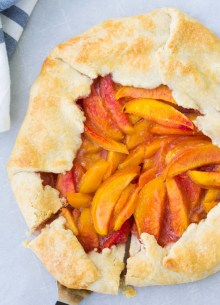 Whole peach galette with a slice cut.