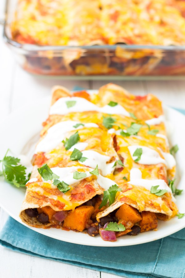 Vegetarian enchiladas with black beans and sweet potato filling on a plate with sour cream.