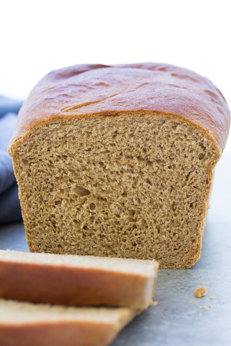 Loaf of whole wheat bread with a few slices in front.
