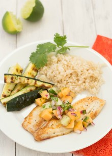 pan seared tilapia on plate with sides of rice and zucchini