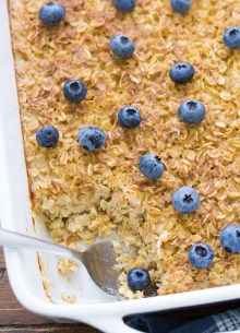Baked oatmeal topped with blueberries in a baking dish with a spoon.