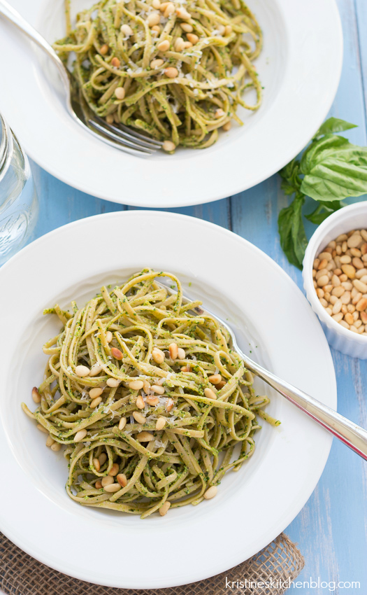 kale pesto over pasta on a white plate with a fork