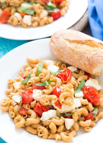 Easy caprese pasta with fresh mozzarella, tomatoes and basil, served with crusty bread.