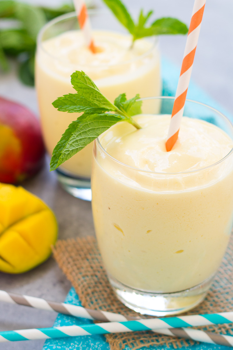 Two creamy mango smoothies in glasses with mango and mint leaves.