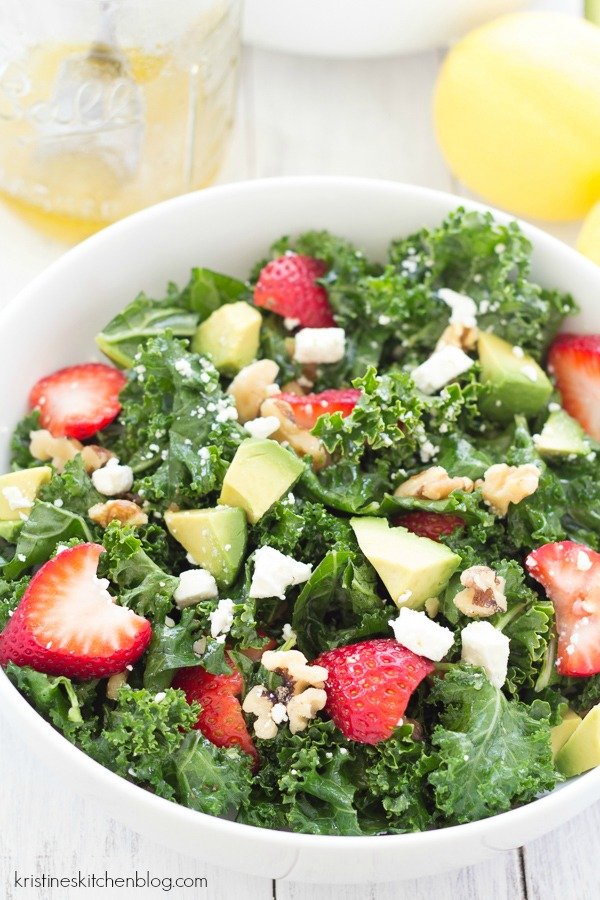 all ingredients for kale salad tossed together and ready to eat in a white bowl