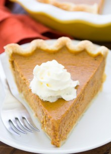 A slice of homemade pumpkin pie with whipped cream on a small plate.